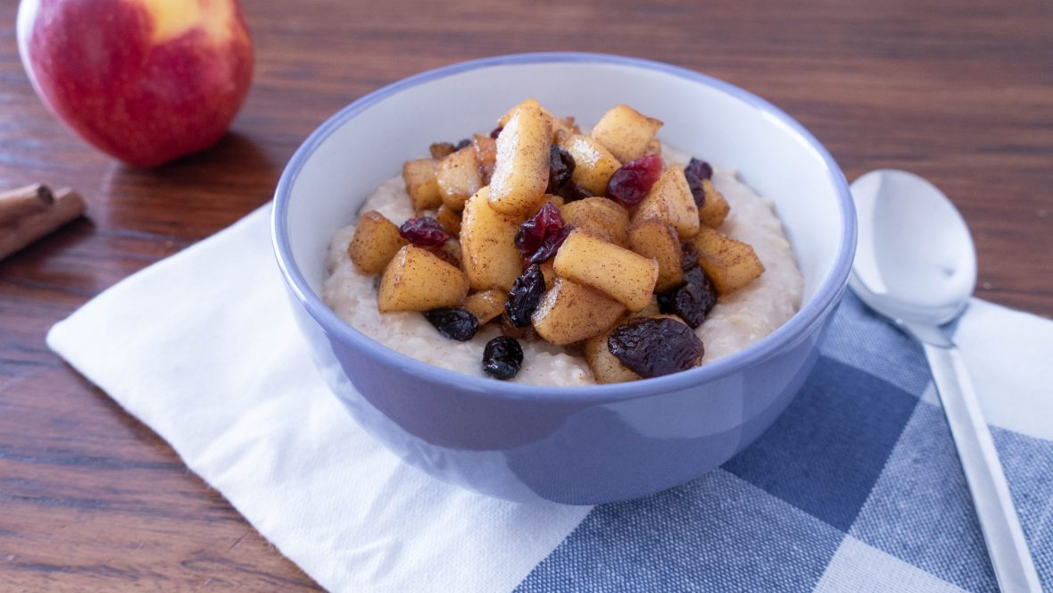 A bowl of rolled oats porridge with mixed sauteed apple and dried fruits on top. A silver spoon on the right and a red apple and two cinnamon sticks on the left