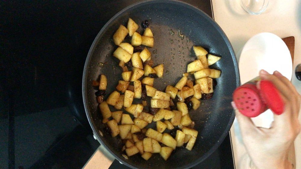 Sprinkling some grounded nutmeg in a pan with diced apple and mixed dried fruits