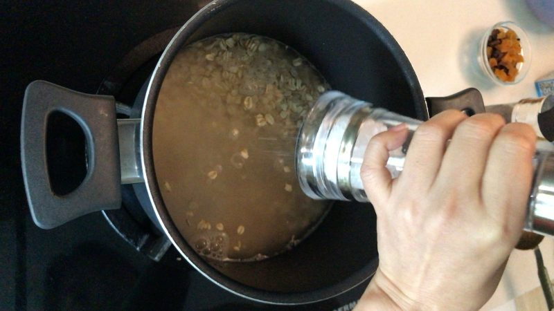 Adding some sea salt in a pot with rolled oats and water inside