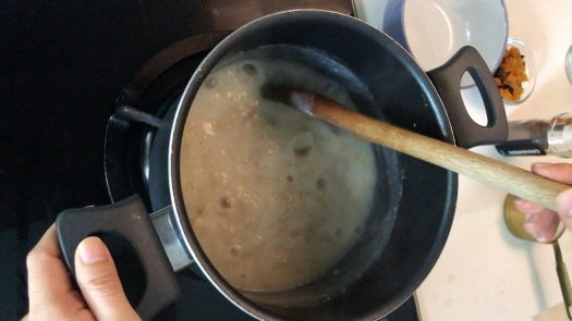 Stirring a pot of boiling rolled oats porridge