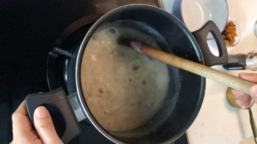 Stirring a pot of boiling rolled oats porridge