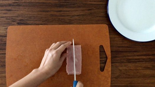 Slicing a piece of ham into four strips on a chopping board
