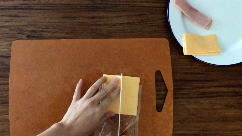 Cutting a piece of sliced Cheddar cheese