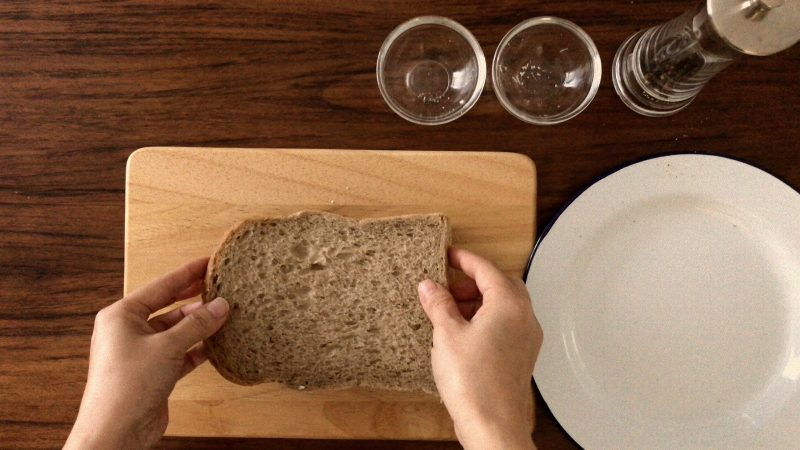 Using another piece of brown bread to cover the open sandwich