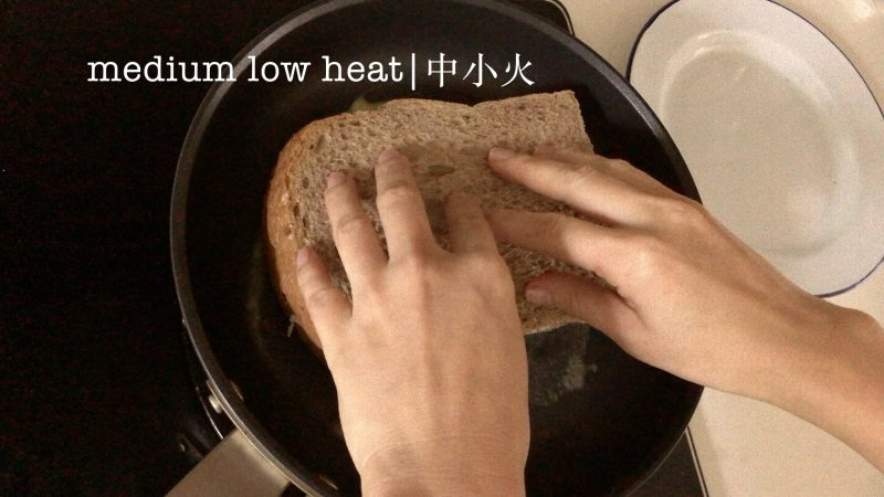 Placing a sandwich into a pan with melted butter