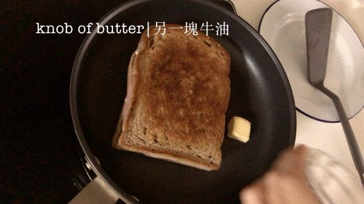 A brown bread sandwich in a pan with a knob of butter next to it