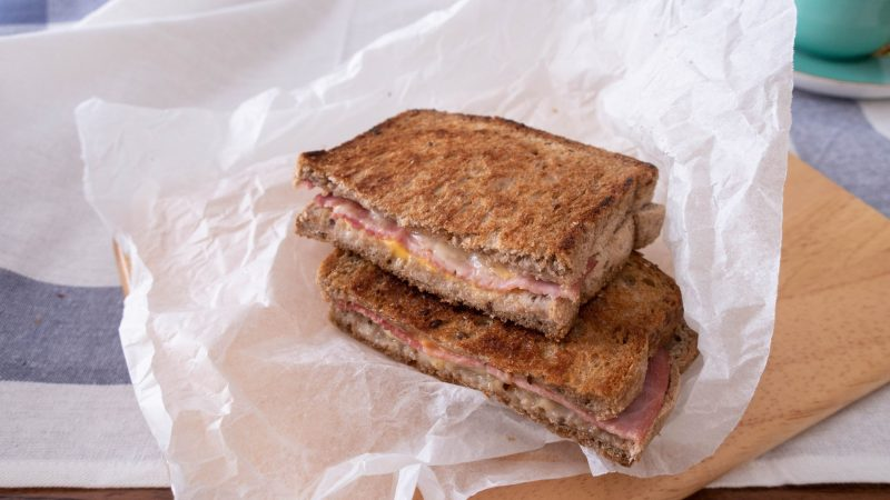 A halved grilled ham and cheese sandwich on a piece of baking paper