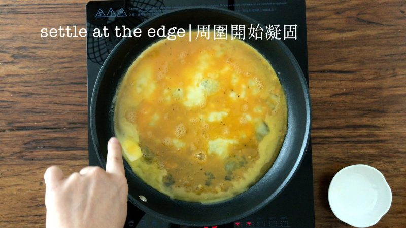 The edge of the eggs in a non-stick pan start to set