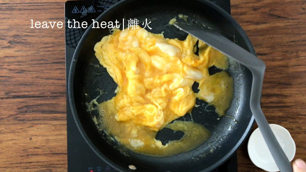 scrambled eggs in a pan is almost cooked