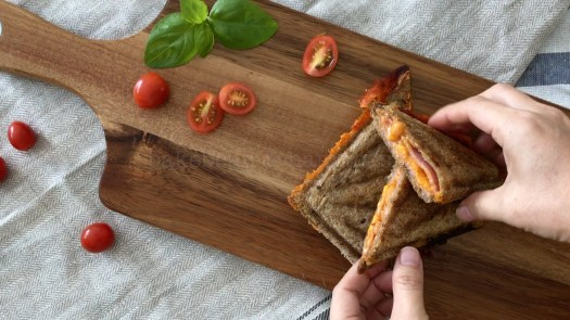 Nice and crunchy ham and baked beans toasties serve on a wooden board