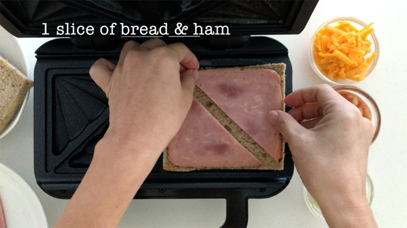 Laying one layer of ham on a slice of brown bread on a toasties maker