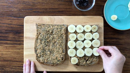 laying sliced banana on one piece of brown bread on top of the peanut butter