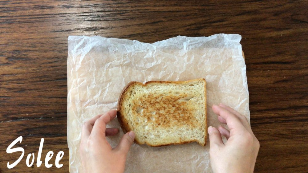 a slice of toasted whole wheat sandwich bread on a board with a piece of cooking paper