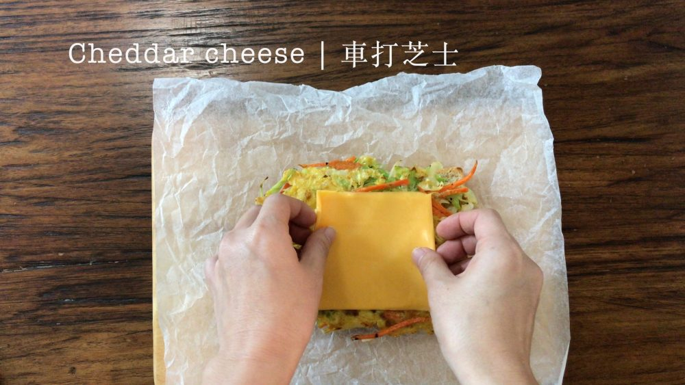 Placing a slice of Cheddar cheese on top of the vegetable pancake