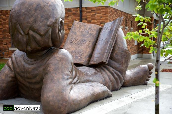 Child reading a book sculpture by Hans Gilsdorf in Detroit Lakes, Minnesota