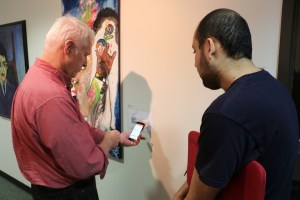 Two men, one with white hair and one with dark hair, looking at a mobile phone in front of artwork