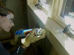 Woman holding Great Stuff window seal from walmart