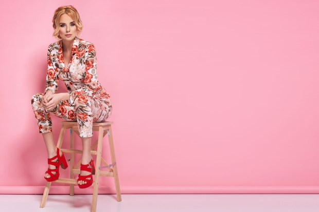 Fashion photo of a beautiful elegant young woman in a pretty suit with flowers holding handbag posing over pink background