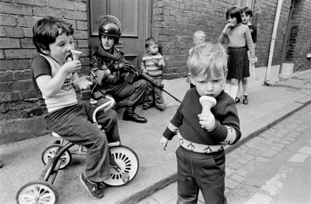 Children eat their ice creams while soldiers patrol the streets of Londonderry 1979