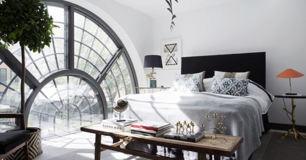 Bedroom with a large spiral window in an apartment inside a converted 17th-century Swedish brewery