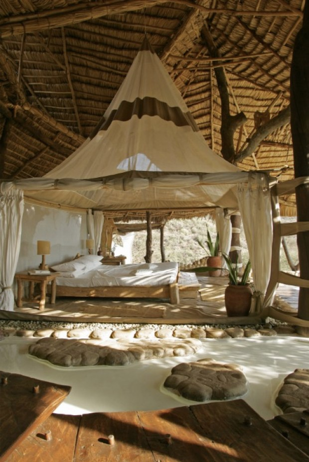 Tented bedroom beneath large thatched roof overlooks the bush in Southern Kenya