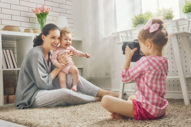 Mother and her daughters children girls playing and making photo