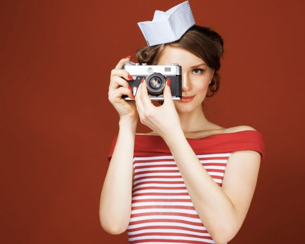 beautiful-pin-up-girl-holding-a-vintage-camera-and-directs-it-straight-to-the-camera