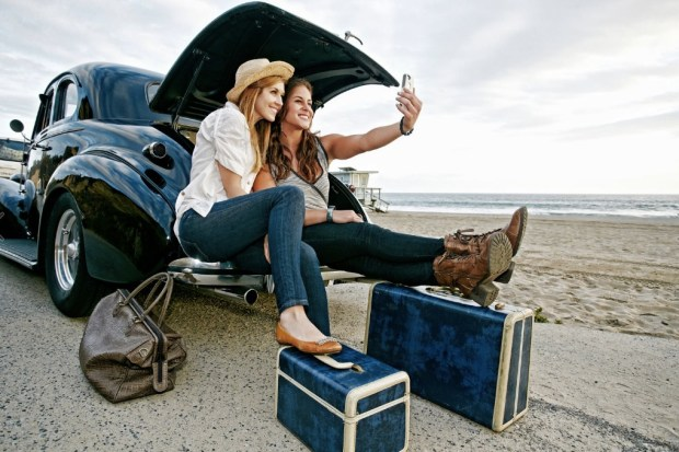 women-with-luggage-and-vintage-car-on-beach
