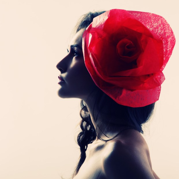 Vintage portrait of fashion glamour girl with red flower in her hair, over white