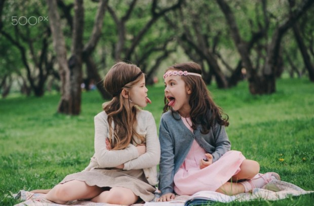 two kid girlfriends showing tongue to each other