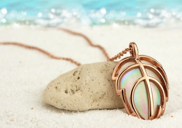 Golden jewellery pendant on summer sand beach with sea background, soft focus