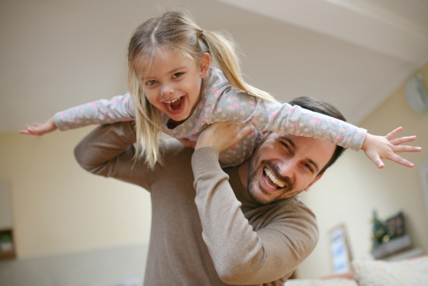 Cute young daughter on a piggy back ride with her dad