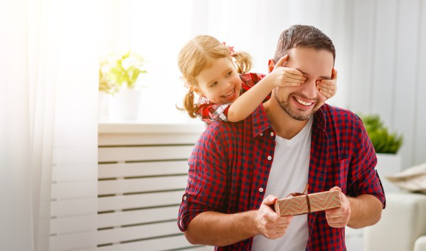 Happy family daughter hugging dad and laughs on holiday