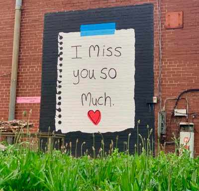 a photo of a mural by gina elizabeth franco that is painted on brick with a black background and an image of a piece of paper torn from a notebook with the words I miss you so much and a small red heart grass is in the foreground of the photo