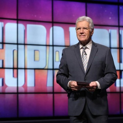 Alex Trebek of Jeopardy standing on stage holding his iPad