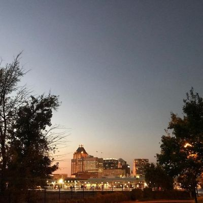 a photo of downtown greensboro at dusk with dark silhouette of trees on either side of the foreground