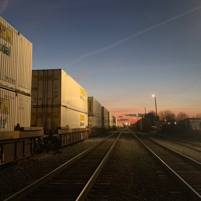 a photo of train cars piled with containers reflecting the glow of the sun at dusk in greensboro nc