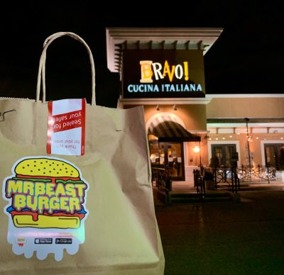 a photo of a to-go bag of mr beast burger in the foreground and bravo restaurant in the background