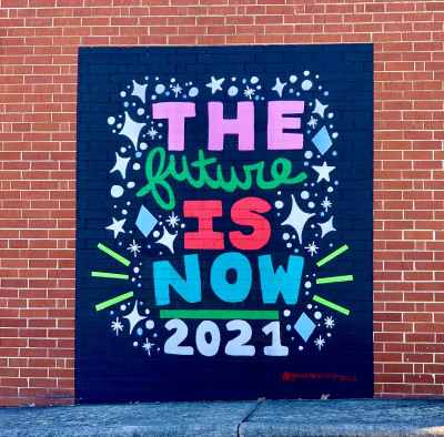 a photo of a mural on the side of a brick wall that says the future is now 2021 by gina elizabeth franco