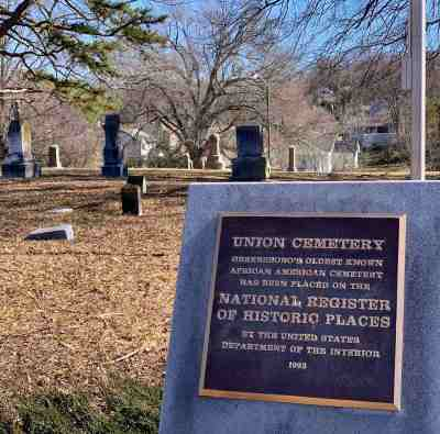 a photo of the plaque at the union cemetery in greensboro nc with grass and gravestones and trees behind it.