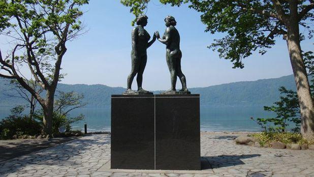 La estatua de dos doncellas de Kōtarō Takamura que está en la orilla del lago Towada.