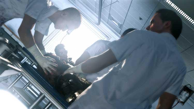 Momento en el que Miller (en el centro, con gafas de sol) se dirige hacia el jugador, preguntando a los médicos por el estado del otro personaje, posteriormente revelado como el protagonista de Phantom Pain. La cámara realiza movimientos que denotan que representa la visión de este otro personaje, que no será otro que Venom Snake, el Big Boss de este juego.