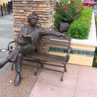 Sculpture of Mark Twain reading book on bench.