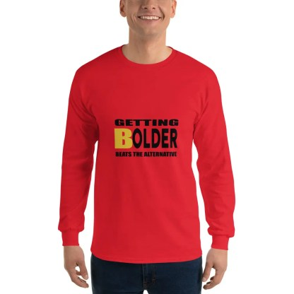 Man with a smile is wearing dark jeans & a long sleeved red t shirt with the slogan getting bolder beats the alternative