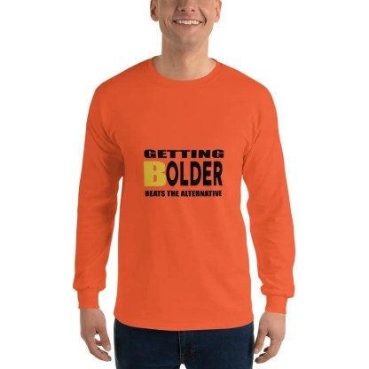 Man with a smile is wearing dark jeans & a long sleeved orange t shirt with the slogan getting bolder beats the alternative