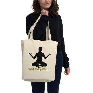 Woman in black holding a natural coloured cotton tote bag with silhouette of woman squatting on toes with the phrase oh my guru underneath