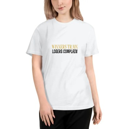 Woman with light brown shoulder length hair wearing black jeans & a white short sleeved t shirt which says winners train losers complain