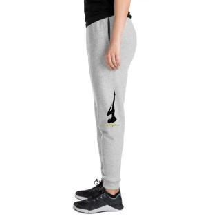 Side view of person wearing dark trainers dark t shirt & gray slim fitting jogging bottoms with silhouette of a yoga pose with the phrase oh my guru underneath on each leg