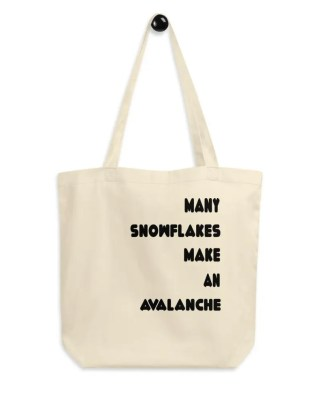 A beige colored cloth bag on a peg with the slogan many snowflakes make an avalanche