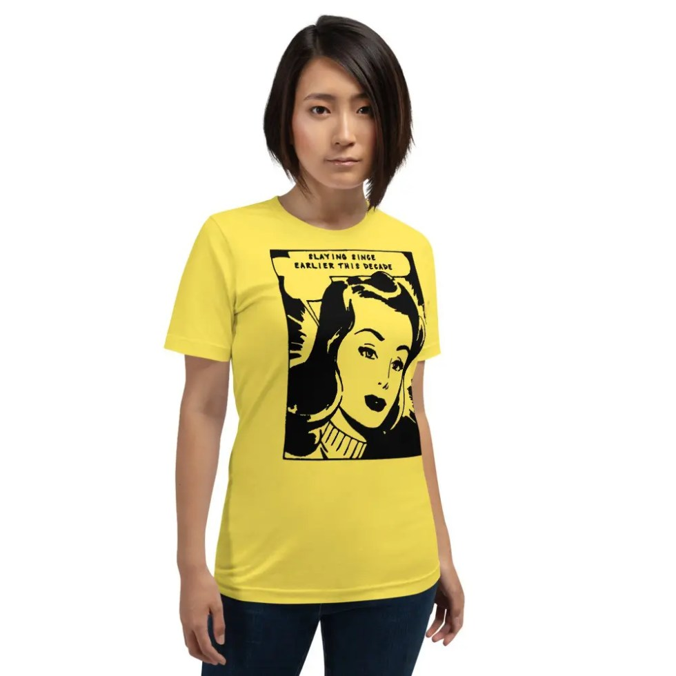 Woman with short dark hair wearing black jeans wearing a yellow short sleeve t shirt with graphic of a woman saying slaying since earlier this decade.